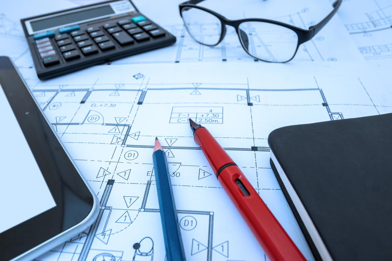 building plan on desk with pens, calculator, eyeglasses, ipad and notebook