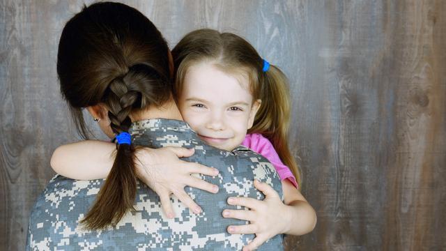 A mother in uniform hugging her daughter. Advocacy for women veterans in Atlanta, Georgia benefits generations.
