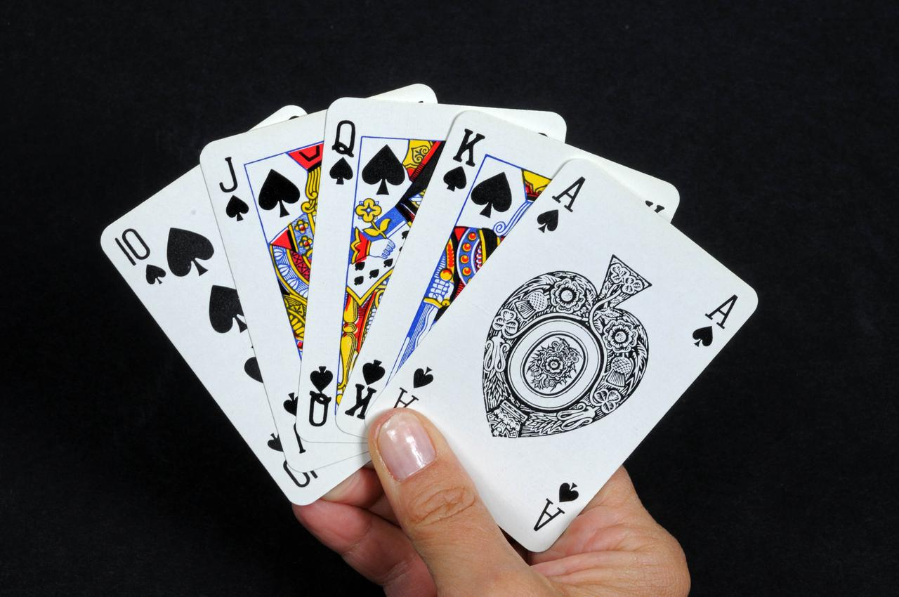 Someone holding a hand of cards, all the same suit.