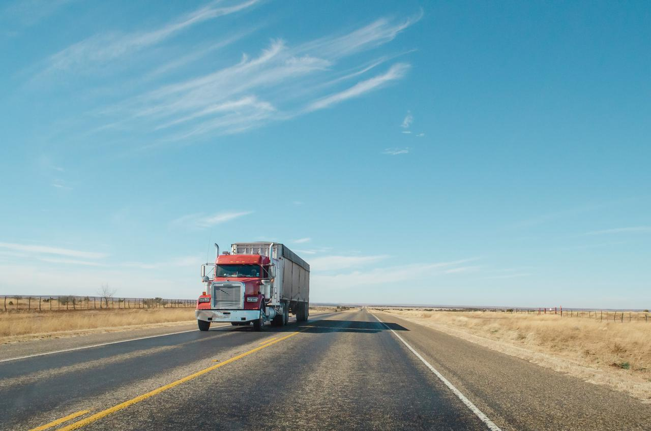 A red semi truck driving down the road in West Texas | Check out my blog: matthewtrader.com/unsplash