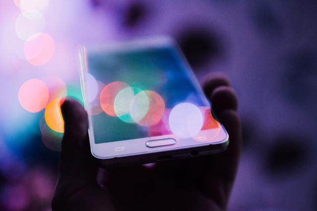 A person holding up a smartphone in their hand with colorful bokeh circles over its screen