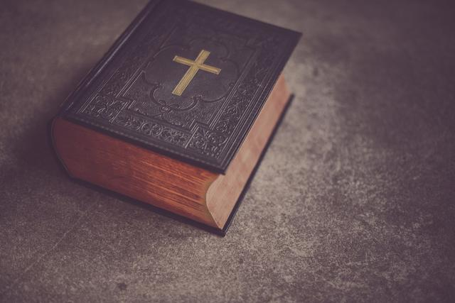 A Bible laying on a flat concrete surface.