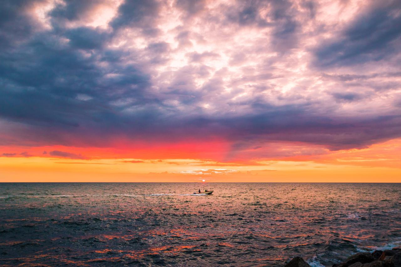 Coloured sunset at sea with small boat sailing