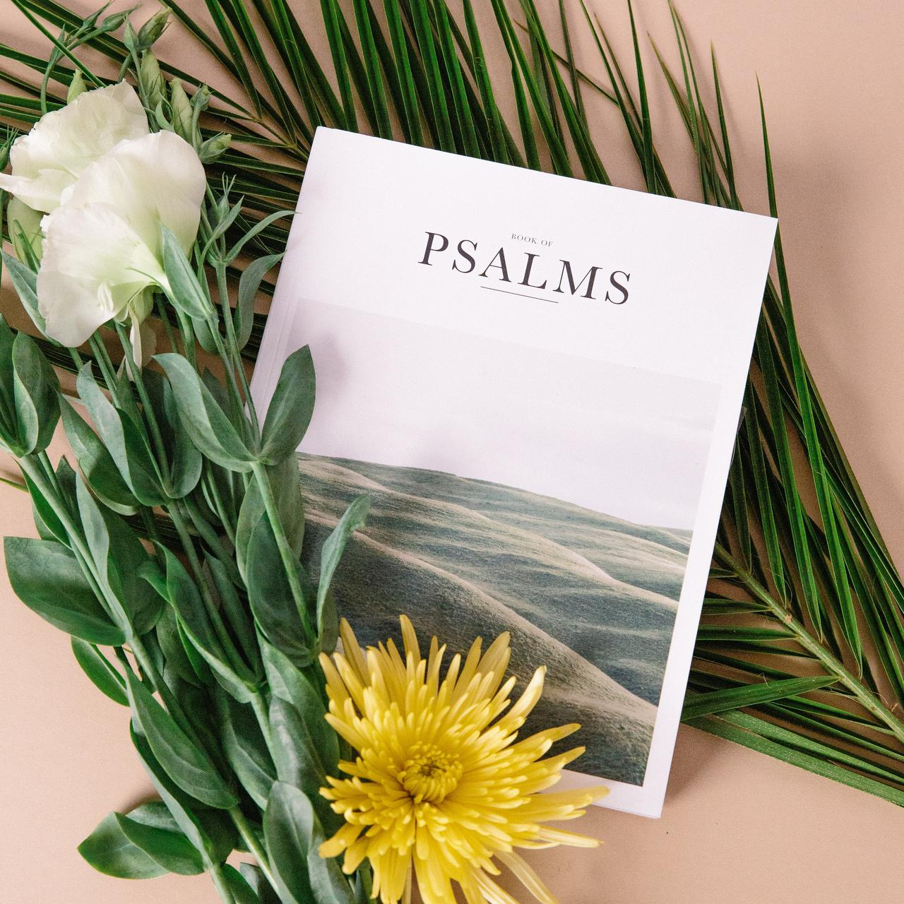Book of Psalms with yellow and white flowers on tan background