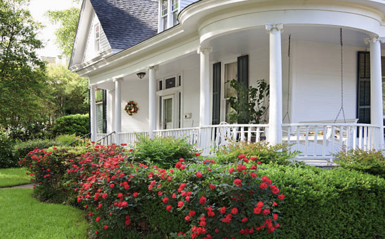 white house with wrap around porch and rose bushes