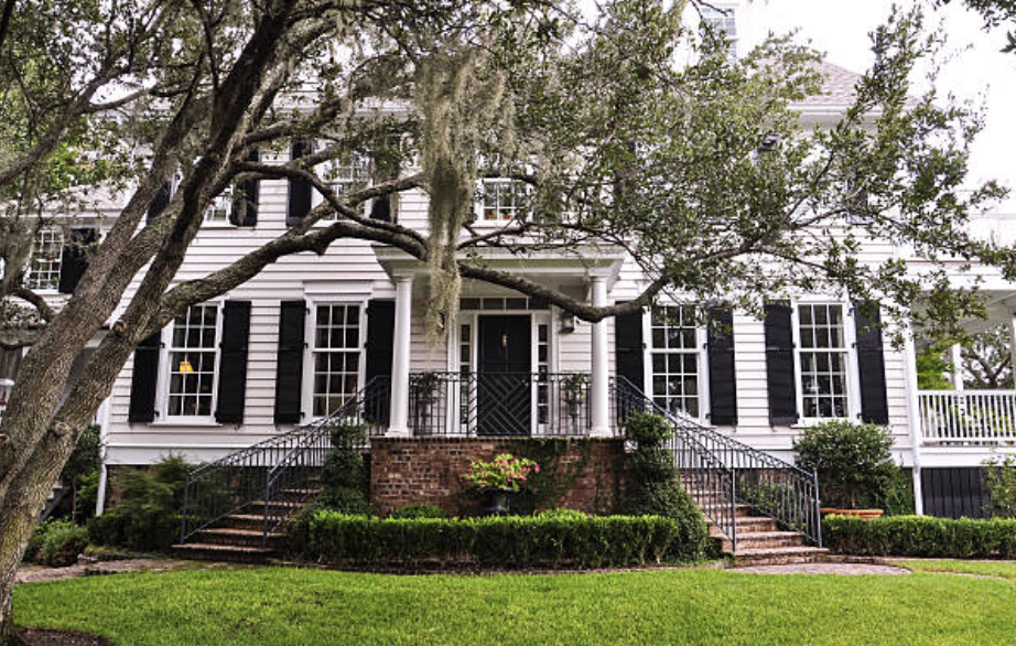 white two-story house with black shutters and large tree in front yard