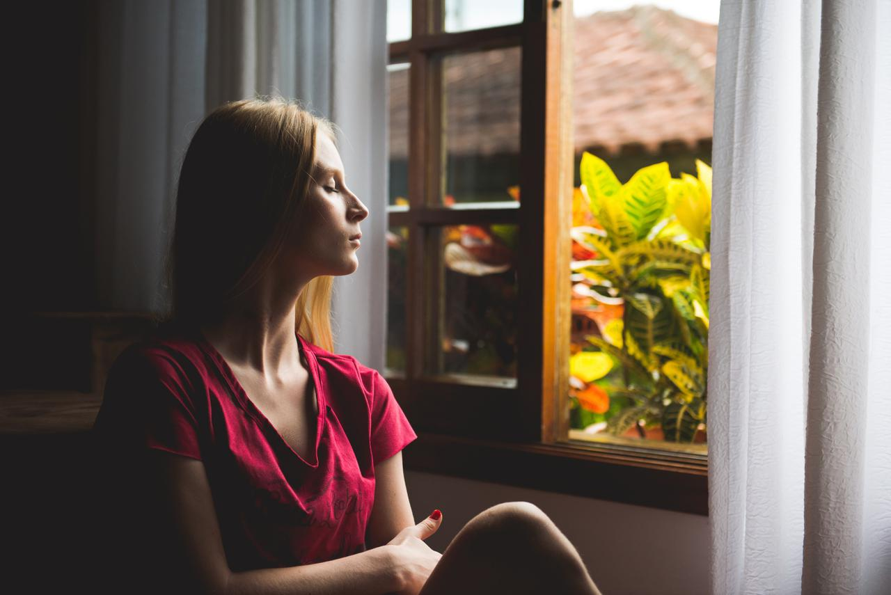 woman sitting near open window