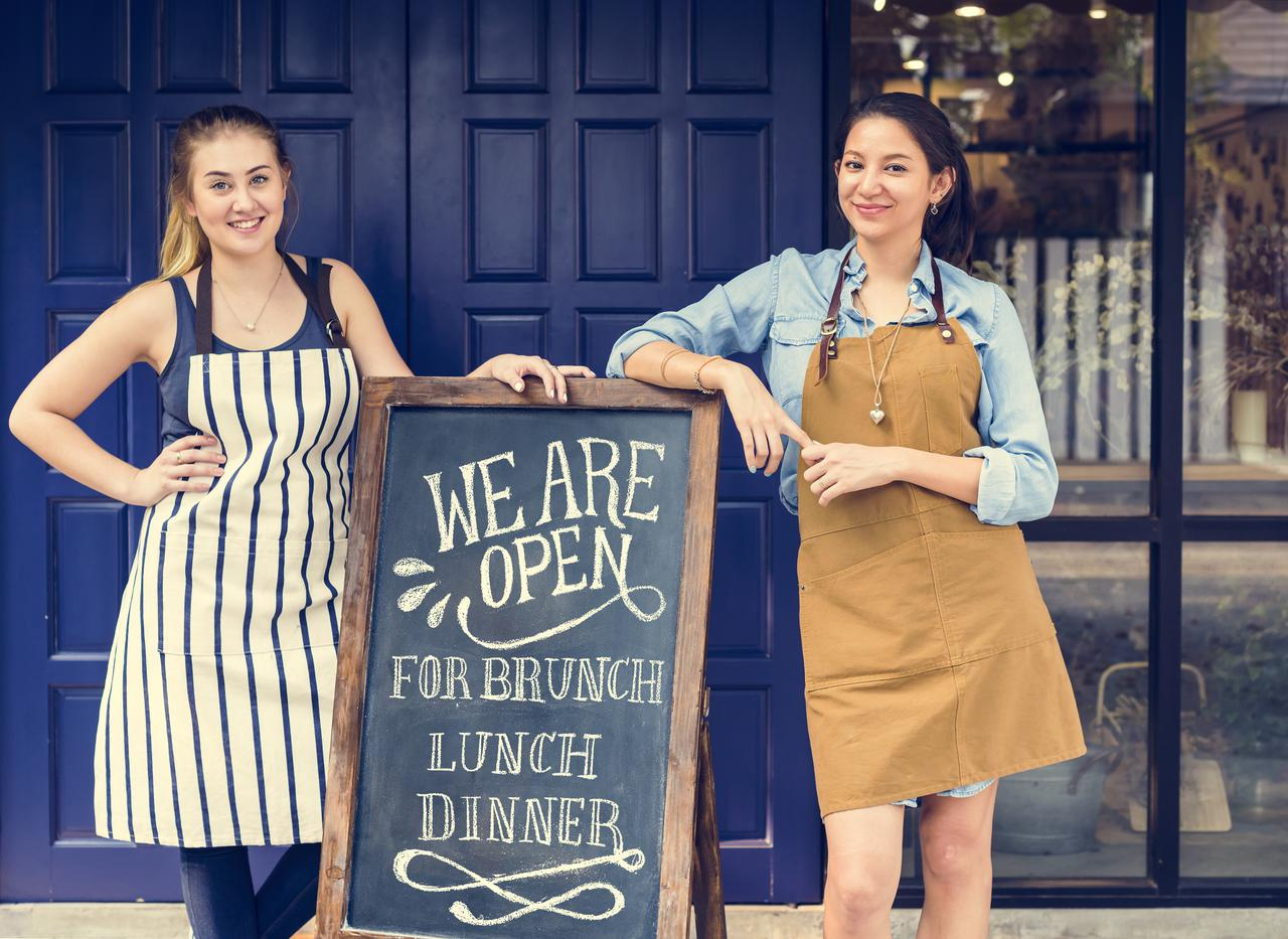 cheerful-business-owners-standing-with-open-P4NYRZB (1).jpg