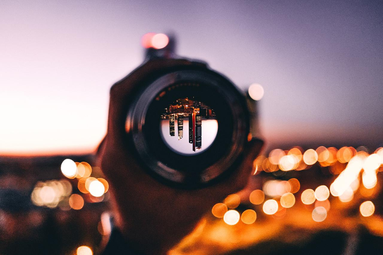 shallow focus photography of person holding camera lens business solutions