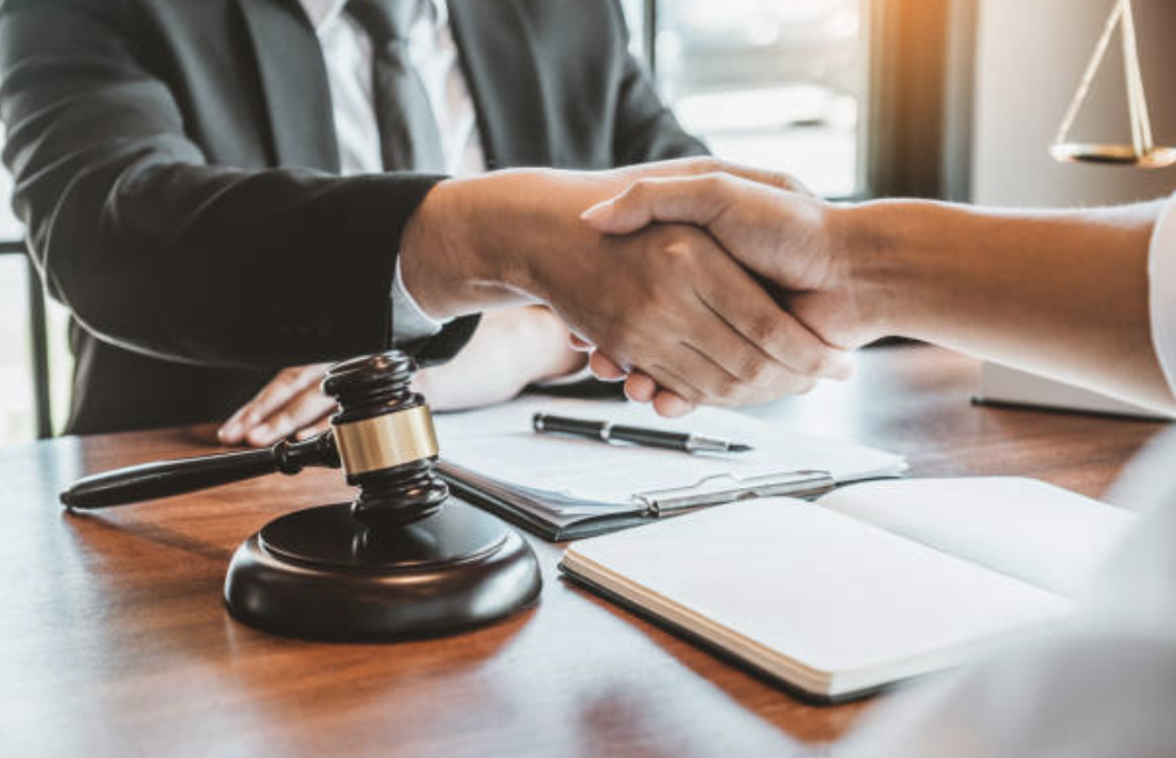 two men shaking hands over a lawyer's desk
