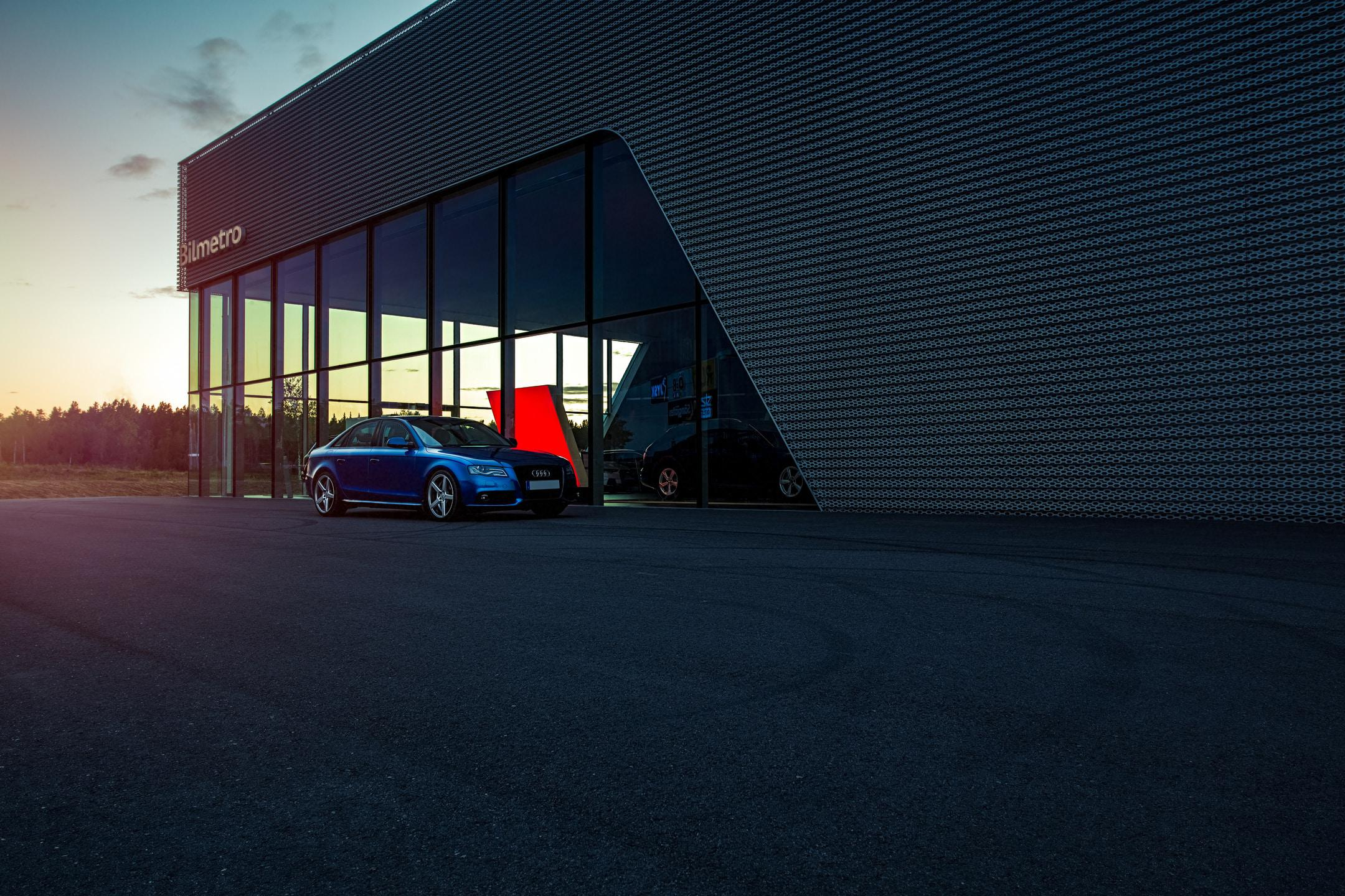 Blue Audi A4 Quattro Saloon Scene with Swedish modern architecture at dealership