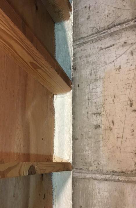 An image of concrete and wood joined by ban / rim joist insulation.