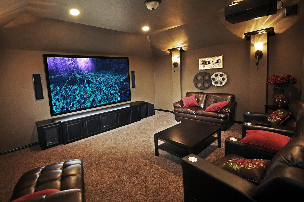 An image of an entertainment room with a big flat screen TV and ample, comfortable leather seats.
