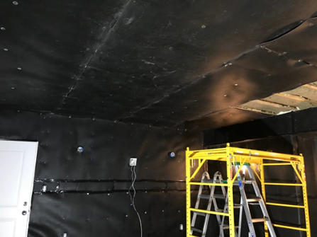 A room with black coverings on the ceiling and wall and a yellow structure encasing a ladder.