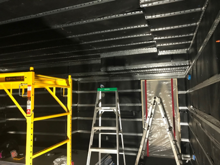 A recently soundproofed room with two ladders sitting in the middle.