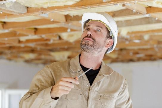 A man with a beard, hardhat, and a screw in one hand looking up at the ceiling.