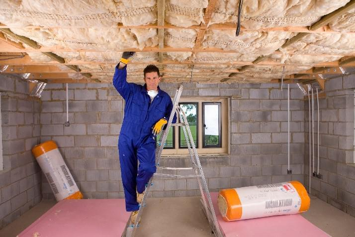 A man in a blue jumpsuit installing insulation in a crawlspace.
