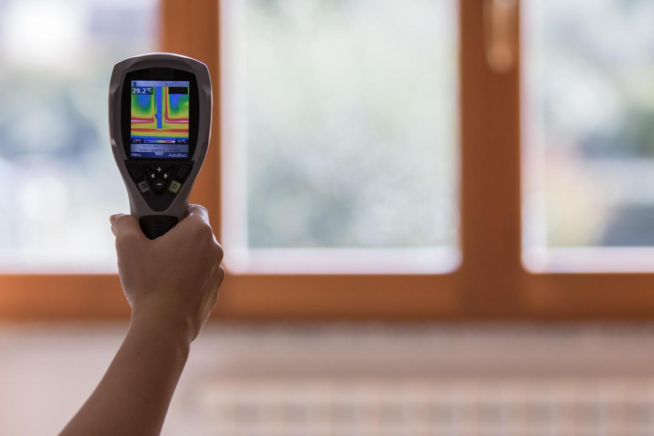 An image of someone measuring the energy efficiency of a home.