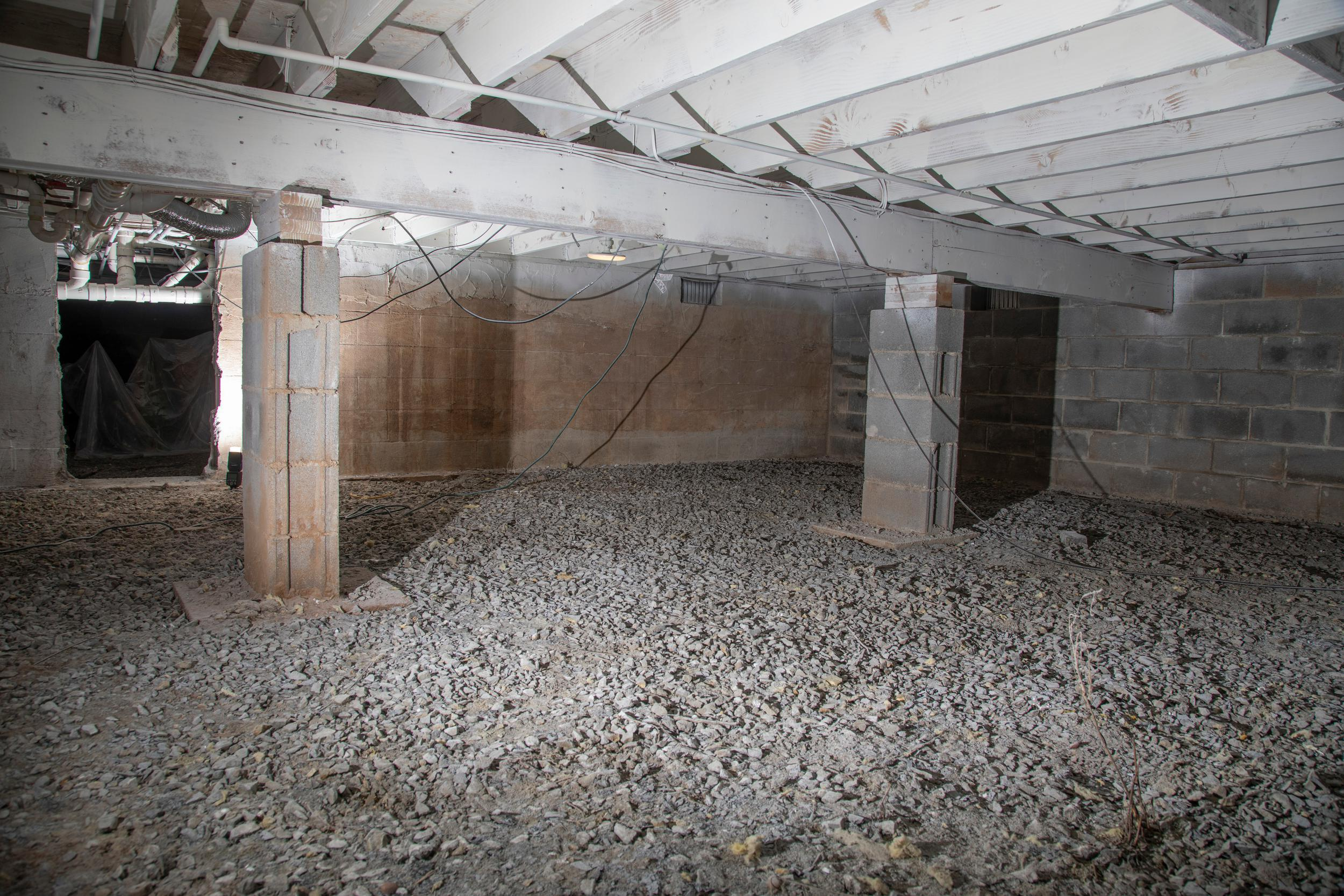 An image of a basement with gravel and rocks and a grey concrete ceiling.