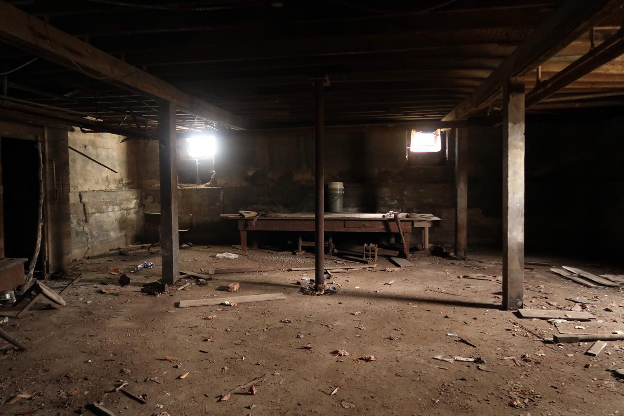 A basement with a table and wood debris on the floor. It needs work.