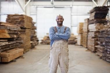 A bald man with overalls and a blue shirt, smiling into the camera.