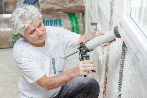 A photo of a man in a white shirt using a white device to apply attic accessories to a white wall.