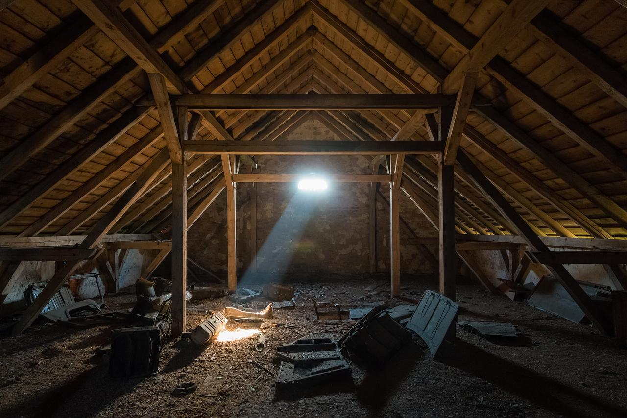 An attic that's disorganized with sun beaming in.