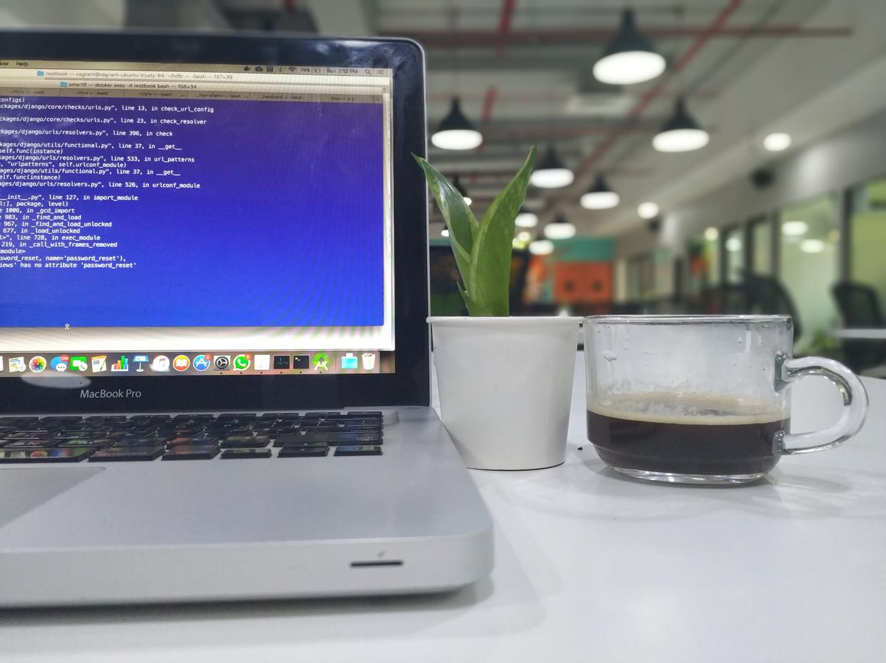 A computer, plant, and half-drunk cup of coffee on a table. An example of small business IT outsourcing services at work.