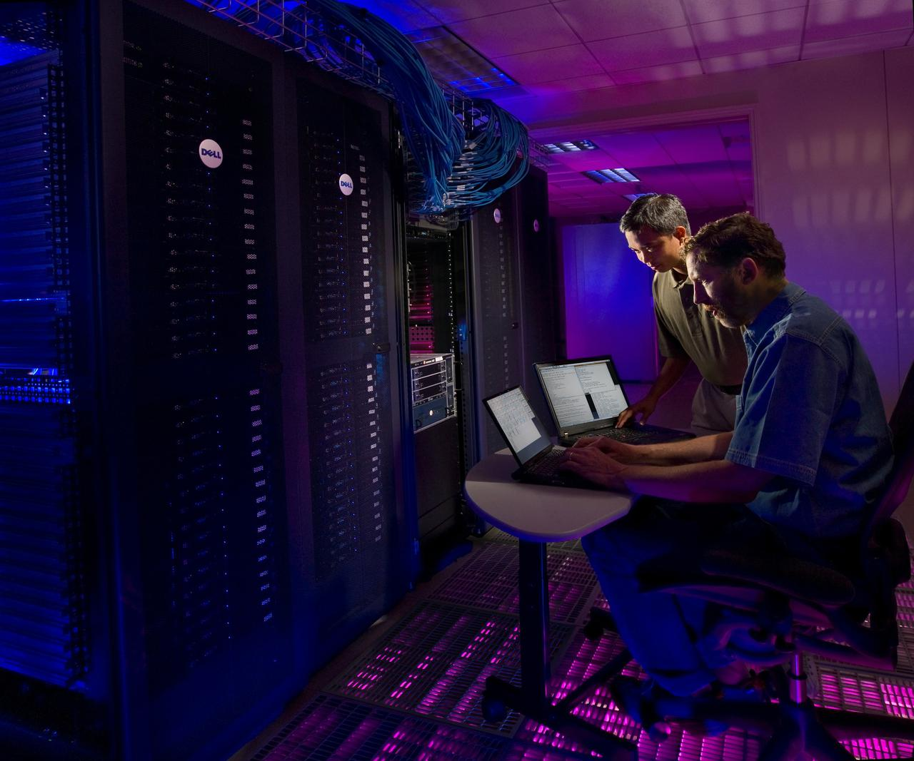 Image of two Medford computer specialists working on a server in a room lit with purple light.