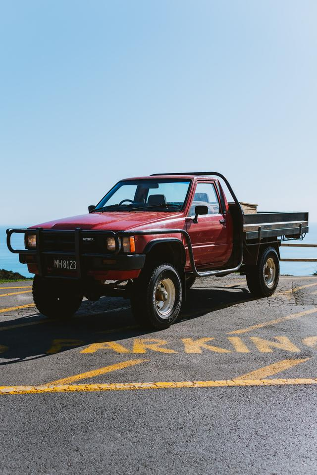 a older red pickup truck with a black truck grille attached to the front