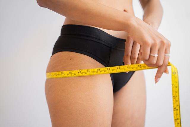 A woman measuring her hip circumference with a tape measure.