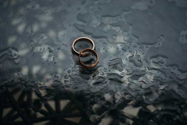 two wedding rings on a wet glassy surface