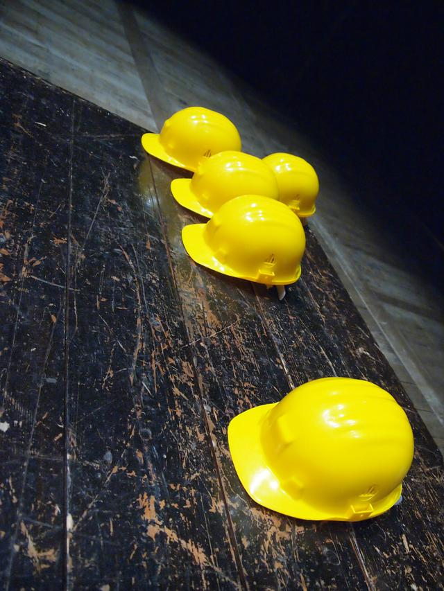 Five yellow construction hats laying on a tile floor.