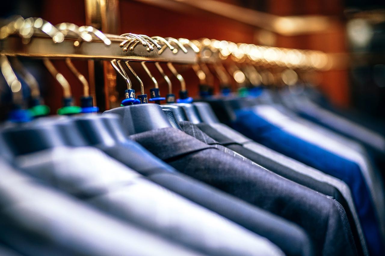 Row of men suit jackets on hangers.
