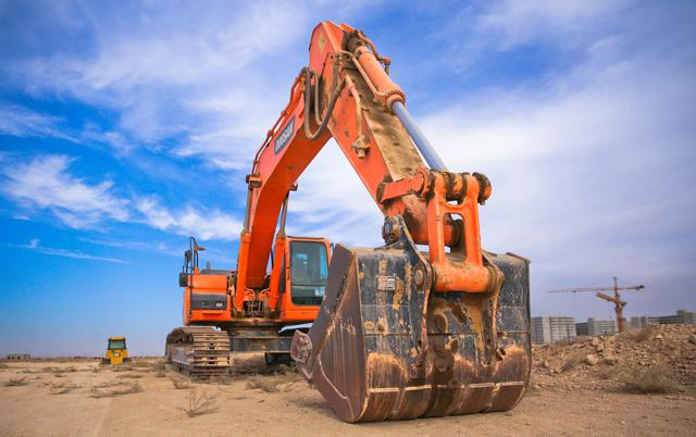low-angle-photography-of-orange-excavator-under-white-clouds-1078884.jpg