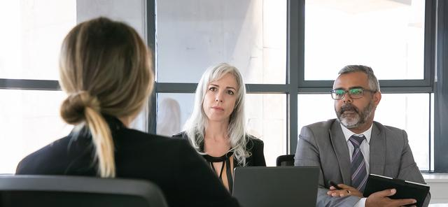A woman talking with two business people. Learning how to implement diversity training in the workplace is crucial to your performance.