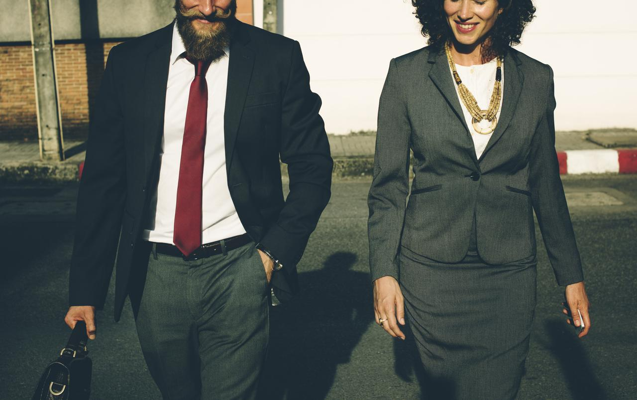 man and woman in business attire walking
