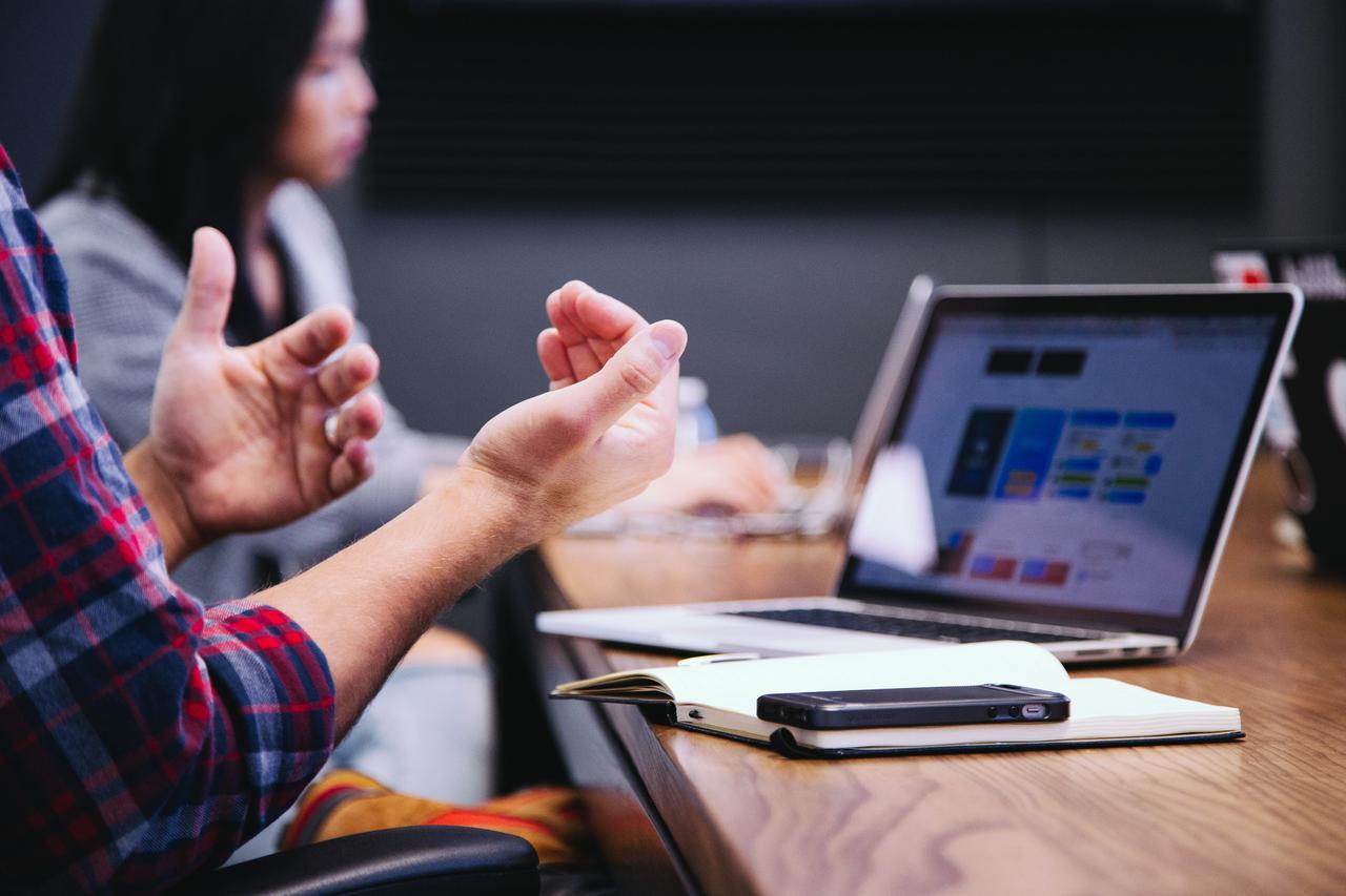 hands gesturing in front of laptop