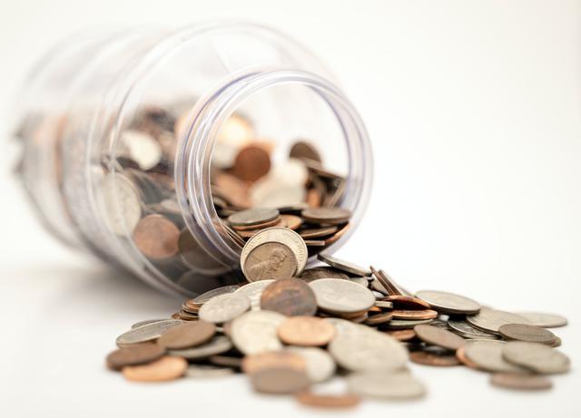 A jar full of coins spilling over.
