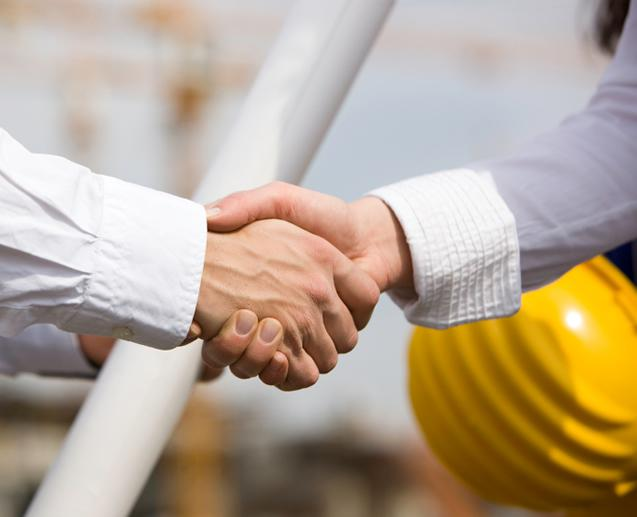 two people shaking hands with a construction hat