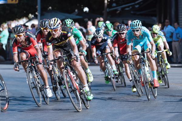 A group of cyclists in helmets in a race along Avenida de la Aurora, with spectators