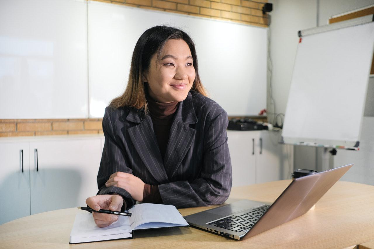 a woman at a desk smiling off to the right of the camera