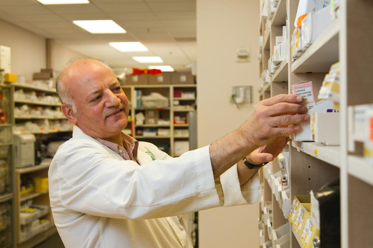 A male pharmacist is selecting a drug from a display case in a pharmacy.