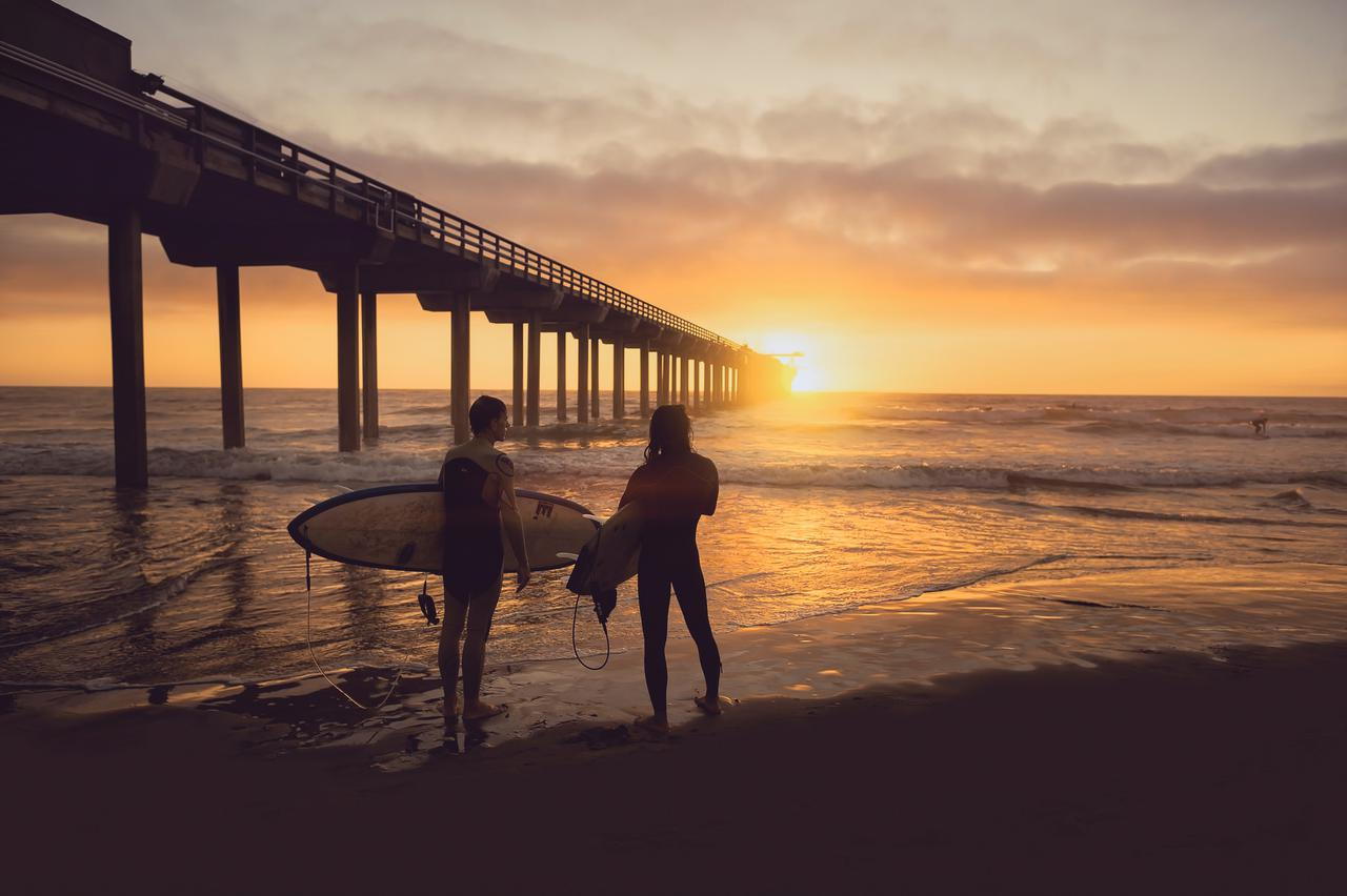 woman carrying surfboard beside person during sunset