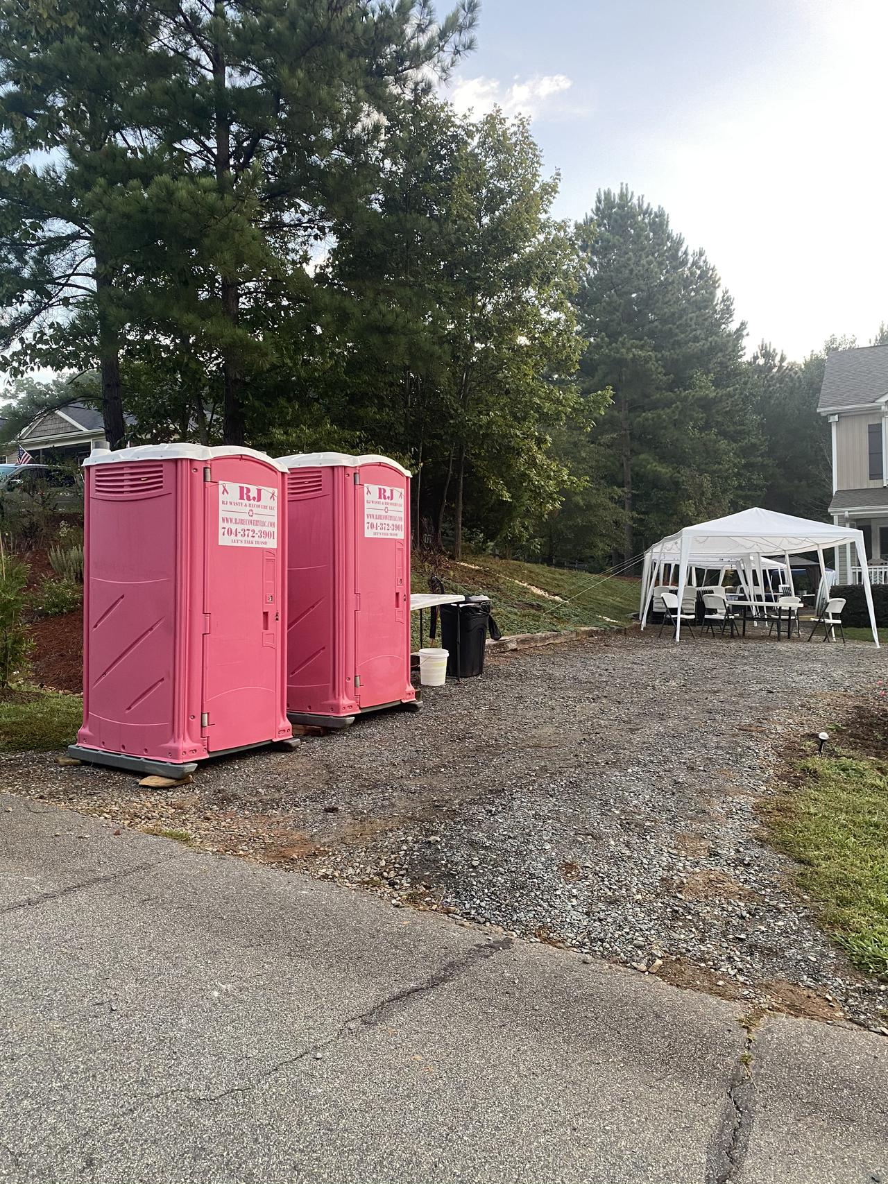two pink RJ Waste & Removal portable toilets in a driveway