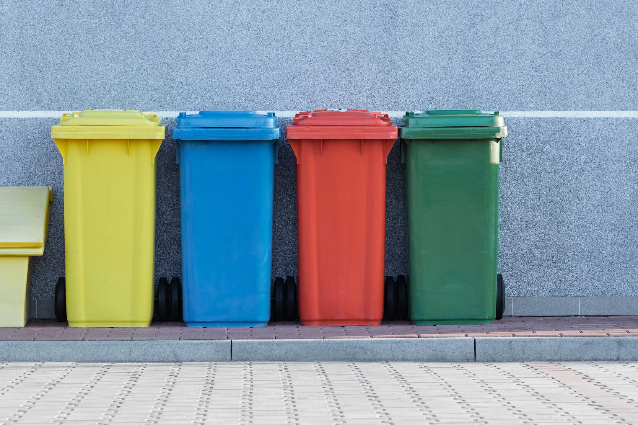 four brightly colored trash bins lined up neatly on a sidewalk