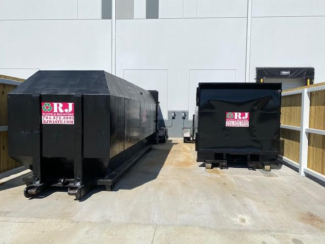 two black RJ Waste & Recovery compactors sitting side by side