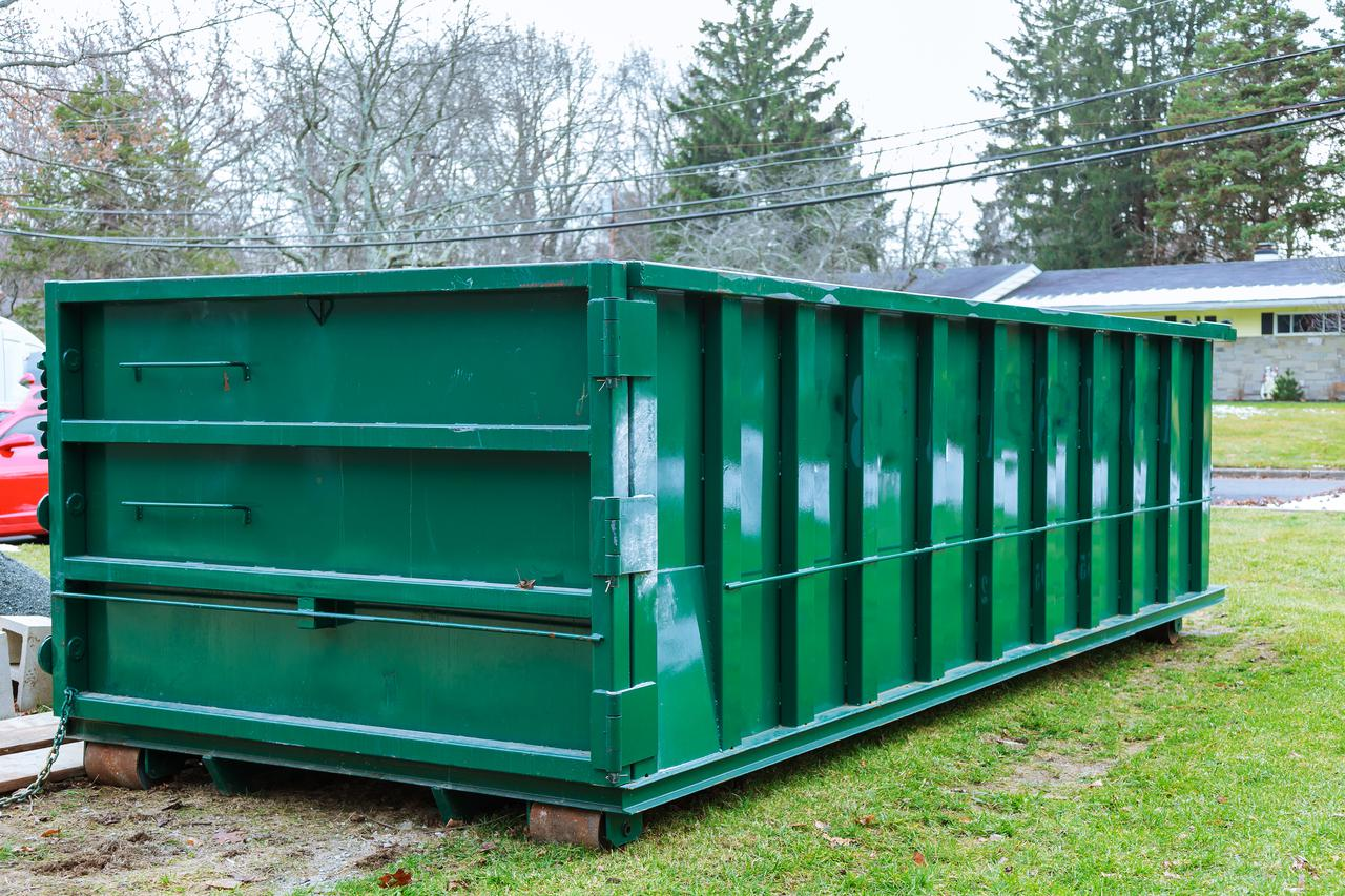 green roll off dumpster sitting in a front yard
