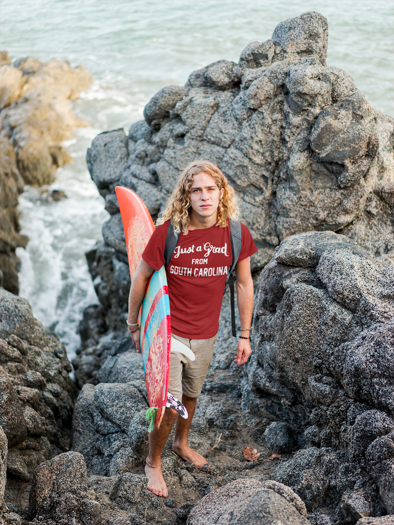 surfer-dude-wearing-a-t-shirt-mockup-on-the-rocks-a18801.png