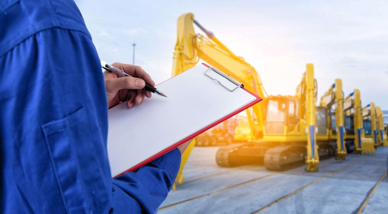 man in blue shirt writing on a clipboard with construction equipment in background